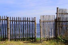 Holzhaus auf dem Strand, Blick durch rustikalen Zaun zum Ozean Lizenzfreie Stockfotografie