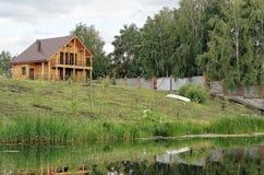 Holzhaus durch den Fluss Lizenzfreie Stockfotografie