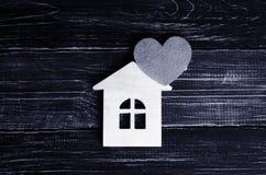 Holzhaus mit einem roten Herzen auf einem Hintergrund von schwarzem hölzernem BO Stockbild