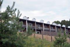 Holzhaus umgeben durch Berge und grünen Koniferenwald Stockbilder