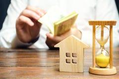 Holzhaus und Uhr Geschäftsmann, der Geld zählt Zahlung der Ablagerung oder Vorauszahlung für das Mieten eines Hauses oder der Woh stockfotografie