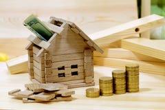 Holzhausblock mit Münzen (Finanz-, Eigentums- und Hausdarlehen Lizenzfreie Stockfotos