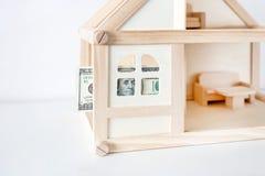Holzhausmodell mit 100 Dollarschein Hausmiete und -verkauf Ausgaben und Kosten für die Hausbehandlung Wohnungseinsparungenskonzep Stockbilder
