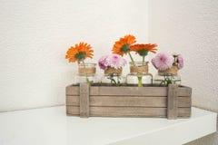 Holzkiste mit den orange und rosa Blumen auf weißem Regal, weißer Hintergrund, moderner Entwurf stockbild