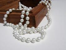Holzkiste mit Detail der Perlenhalskette auf weißem Hintergrund Lizenzfreie Stockfotos