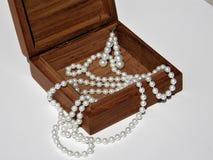 Holzkiste mit Halskette und Ohrringen von den Perlen herein Stockfotos