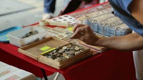 Holzkiste mit vielen alten Münzen auf Tabelle, männliche touristische wählende Andenken stock footage