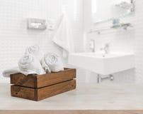 Holzkiste mit weißen Badekurorttüchern auf unscharfem Badezimmerhintergrund Lizenzfreies Stockbild