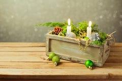 Holzkiste mit Weihnachtsdekorationen und -kerzen über träumerischem Hintergrund Weihnachtstabellenaufbau Lizenzfreie Stockfotos