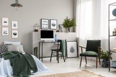 Holzkiste unter einzelnem Metallbett mit blauen Blättern und grüner Decke im modischen Raum des Kindes mit Arbeitsplatz stockfotografie