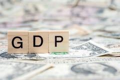 Holzklotz BIP oder des Bruttoinlandsprodukts auf US-Dollar Banknote Lizenzfreies Stockfoto