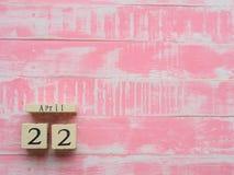 Holzklotzkalender für Welttag der erde am 22. April, helles Rosa Lizenzfreies Stockfoto