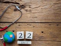 Holzklotzkalender für Welttag der erde am 22. April, Stethoskop Lizenzfreie Stockbilder