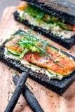 Holzkohlen-Brot geräucherter Salmon Sandwiches auf hölzernem Brett Lizenzfreie Stockfotografie
