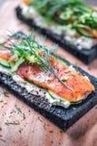 Holzkohlen-Brot geräucherter Salmon Sandwiches auf hölzernem Brett Stockfotografie