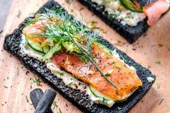 Holzkohlen-Brot geräucherter Salmon Sandwiches auf hölzernem Brett Stockfotos