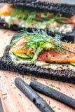 Holzkohlen-Brot geräucherter Salmon Sandwiches auf hölzernem Brett Lizenzfreies Stockfoto