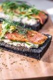 Holzkohlen-Brot geräucherter Salmon Sandwiches auf hölzernem Brett Stockfoto