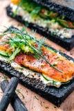 Holzkohlen-Brot geräucherter Salmon Sandwiches auf hölzernem Brett Stockbilder