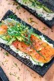 Holzkohlen-Brot geräucherter Salmon Sandwiches auf hölzernem Brett Stockbild