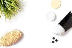 Holzkohlengesichtsmaske und im Rohr mit einer hölzernen Körperbürste, einem Schrubben und einem skincare Konzept, Kopienraum sich lizenzfreie stockfotografie