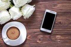 Holzoberfläche mit Blumenstrauß von Rosen, von Tasse Kaffee und von Telefon Romantische Tapete für einen Desktop Lizenzfreie Stockbilder