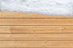 Holzoberfläche mit Schnee auf einer Seite Stockfoto