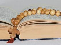 Holzperlen mit einem Kreuz auf offenem Buch Stockbild