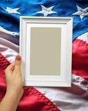 Holzrahmen in den Frauenhänden auf dem Hintergrund der Flatternflagge USA mit Welle Lizenzfreie Stockbilder