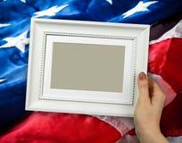 Holzrahmen in den Frauenhänden auf dem Hintergrund der Flatternflagge USA mit Welle Stockfoto