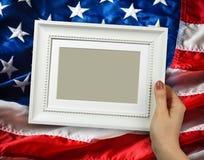 Holzrahmen in den Frauenhänden auf dem Hintergrund der Flatternflagge USA mit Welle Lizenzfreies Stockfoto