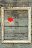 Holzrahmen der Weinlese mit rotem Herzen auf einem Schmutzhintergrund Lizenzfreies Stockfoto