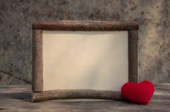 Holzrahmen der Weinleseart mit Herzen auf dem Holztisch stockfotografie