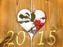 2015, Holzrahmen in Form eines Herzens und Niederlassung der Stechpalme Stockbilder