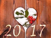 2017, Holzrahmen in Form eines Herzens und Niederlassung der Stechpalme unter dem Schnee Lizenzfreie Stockfotos