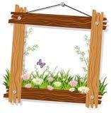 Holzrahmenschablone mit Blumen und Gras Stockbilder