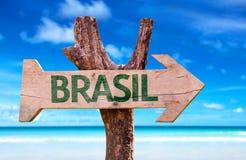 Holzschild Brasiliens (auf portugiesisch) mit einem Strand auf Hintergrund Lizenzfreie Stockfotos