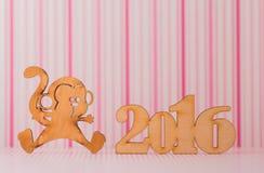 Holzschild des Affen und der Aufschrift von 2016-jährigem auf rosa Streifen Lizenzfreie Stockfotos