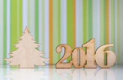 Holzschild des 2016-jährigem und Weihnachtsbaums auf grünem gestreiftem BAC Lizenzfreies Stockbild