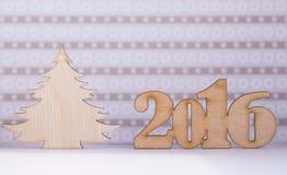 Holzschild des 2016-jährigem und Weihnachtsbaums auf lila Hintergrund Stockfotografie