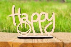 Holzschild glücklich auf dem Tisch und grüner Hintergrund lizenzfreies stockfoto