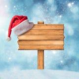 Holzschild und Santa Claus Hat über schneebedecktem Hintergrund Stockfotografie