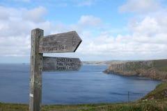 Holzschild, welches die Weise entlang den drastischen clifftops des Küstenweges, Pembrokeshire, Wales zeigt Stockfotos