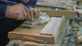 Holzschnitzer schnitzt eine Eichenplanke auf seiner Tabelle stock video