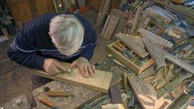 Holzschnitzer schnitzt eine Eichenplanke stock video footage