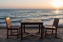 Holzstühle auf dem Strand bei Sonnenaufgang mit einem tropischen Meer Stockbilder