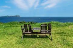 Holzstühle auf Graswiese mit Ansicht über Ozean und Udo Island, Jeju-Insel, Südkorea stockfotografie