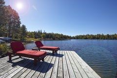 Holzstühle, die einen See übersehen Stockfotos