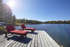 Holzstühle, die einen See übersehen Lizenzfreies Stockfoto