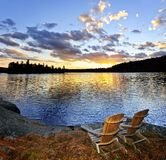 Holzstühle am Sonnenuntergang auf Strand Stockbild